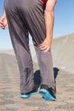 Hombre mayor activo que toca su rodilla herida Foto de archivo libre de regalías