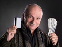 Hombre mayor afortunado que sostiene billetes de dólar y la tarjeta de crédito Imagen de archivo