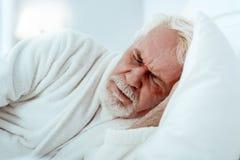 Hombre mayor agitado que ve sueños foto de archivo