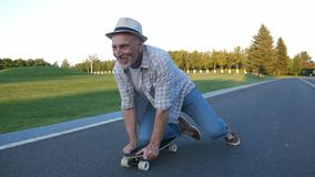 Hombre mayor alegre que anda en monopatín en rodilla en parque metrajes