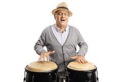 Hombre mayor alegre que juega los tambores del conga imagenes de archivo
