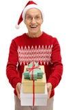Hombre mayor alegre que lleva un sombrero de santa que da presentes Imagen de archivo