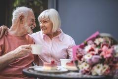 Hombre mayor alegre y mujer que se sientan en la tabla en café foto de archivo libre de regalías