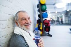 Hombre mayor apto en el gimnasio que descansa después de resolver Imagenes de archivo