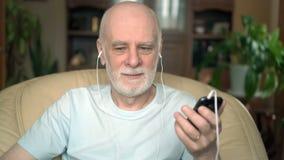 Hombre mayor apuesto que se sienta en silla en casa Música que escucha en smartphone con los auriculares almacen de video