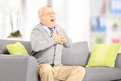 Hombre mayor asentado en el sofá que tiene un ataque del corazón en casa imágenes de archivo libres de regalías