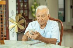 Hombre mayor asiático feliz que usa el teléfono móvil Imágenes de archivo libres de regalías