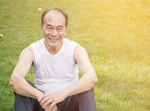 Hombre mayor asiático que se sienta en la hierba verde, prado Foto de archivo