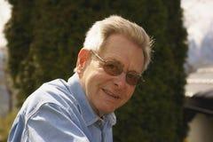 Hombre mayor atractivo amistoso en vidrios Imagen de archivo libre de regalías