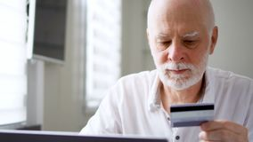 Hombre mayor barbudo hermoso que se sienta en casa El hacer compras en línea con la tarjeta de crédito en el ordenador portátil metrajes