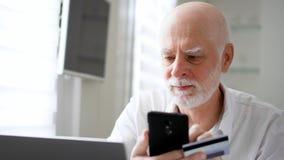 Hombre mayor barbudo hermoso que se sienta en casa El hacer compras en línea con la tarjeta de crédito en smartphone almacen de metraje de vídeo