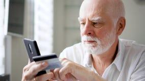 Hombre mayor barbudo hermoso que se sienta en casa El hacer compras en línea con la tarjeta de crédito en smartphone almacen de video
