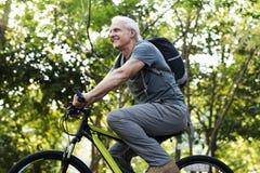 Hombre mayor biking en el parque fotos de archivo