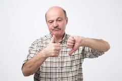Hombre mayor calvo que muestra los pulgares para arriba y los pulgares abajo fotos de archivo