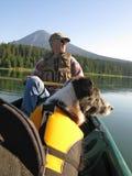 Hombre mayor canoeing con el perro Imagenes de archivo