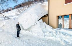Hombre mayor cerca de la entrada de la casa ocultada debajo de la nieve Imagen de archivo libre de regalías