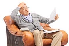 Hombre mayor chocado que mira sus cuentas con incredulidad Imagen de archivo libre de regalías