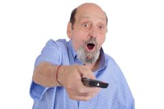 Hombre mayor chocado que ve la TV con teledirigido Imagen de archivo