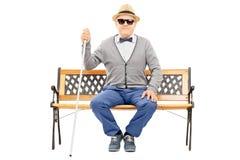 Hombre mayor ciego asentado en el banco aislado en blanco Foto de archivo libre de regalías