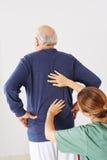 Hombre mayor con dolor de espalda en terapia física imágenes de archivo libres de regalías