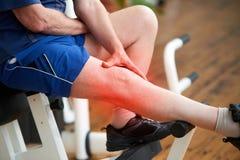 Hombre mayor con dolor de la rodilla en el gimnasio fotos de archivo