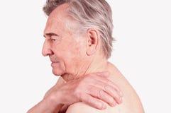 Hombre mayor con dolor en el hombro fotos de archivo