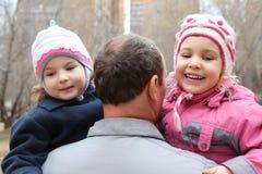 Hombre mayor con dos niños en las manos de la parte posterior Foto de archivo libre de regalías