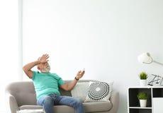 Hombre mayor con el acondicionador de aire teledirigido imagen de archivo libre de regalías