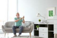 Hombre mayor con el acondicionador de aire teledirigido foto de archivo