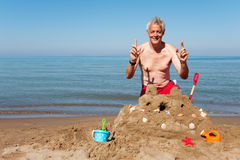 Hombre mayor con el castillo de la arena Imagenes de archivo