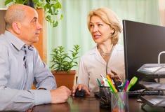 Hombre mayor con el doctor en clínica imágenes de archivo libres de regalías