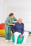 Hombre mayor con el dolor detrás en terapia física fotografía de archivo
