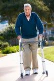 Hombre mayor con el marco que recorre Fotografía de archivo