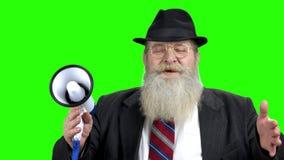 Hombre mayor con el megáfono en la pantalla verde almacen de video