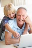 Hombre mayor con el muchacho joven que usa el ordenador portátil Fotos de archivo