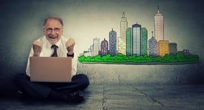 Hombre mayor con el ordenador portátil que busca para el apartamento fotos de archivo