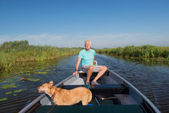 Hombre mayor con el perro en barco de motor Fotos de archivo libres de regalías