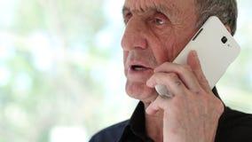 Hombre mayor con el smartphone blanco cerca de la ventana almacen de metraje de vídeo