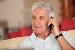Hombre mayor con el teléfono Imagenes de archivo