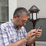 Hombre mayor con el teléfono elegante Imagen de archivo libre de regalías