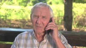 Hombre mayor con el teléfono móvil almacen de video