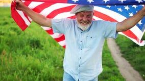Hombre mayor con la bandera americana en un fondo de la hierba verde Los E.E.U.U. D?a de la Independencia celebraci?n 4 de julio almacen de metraje de vídeo