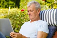 Hombre mayor con la computadora portátil Fotografía de archivo