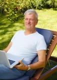 Hombre mayor con la computadora portátil Fotografía de archivo libre de regalías