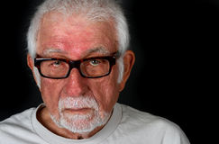Hombre mayor con la expresión triste que vierte un rasgón Foto de archivo
