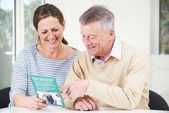 Hombre mayor con la hija adulta que mira el folleto para Retiremen Fotografía de archivo libre de regalías