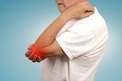 Hombre mayor con la inflamación del codo coloreado en el sufrimiento rojo del dolor Imagen de archivo libre de regalías