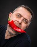 Hombre mayor con la pimienta roja en su boca Foto de archivo libre de regalías
