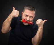 Hombre mayor con la pimienta roja en su boca Imagen de archivo