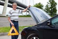 Hombre mayor con la señal de peligro cerca del coche quebrado Fotografía de archivo libre de regalías